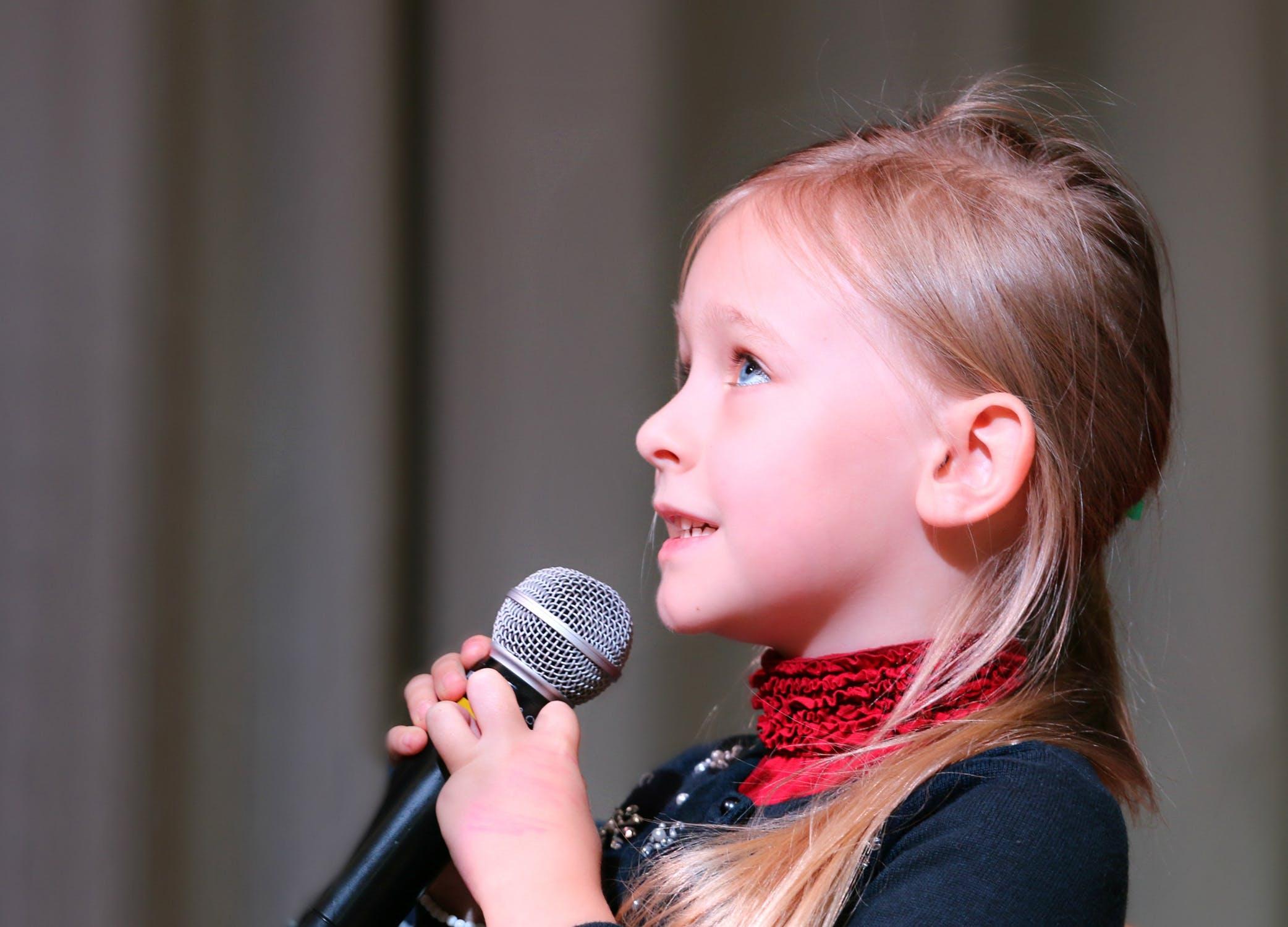 lille pige med mikrofon i hånden